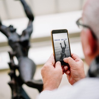 Man is looking at the Zadkine by the Sea app on his phone
